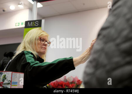 An older female worker working at a till on the checkout counter in M&S Marks and Spencer food grocery store in Great Britain UK. KATHY DEWITT - Stock Image