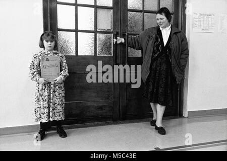 Young girl holding prize certificate as lady keeps door closed at small eisteddfod in village hall at Llandudoch - Stock Image