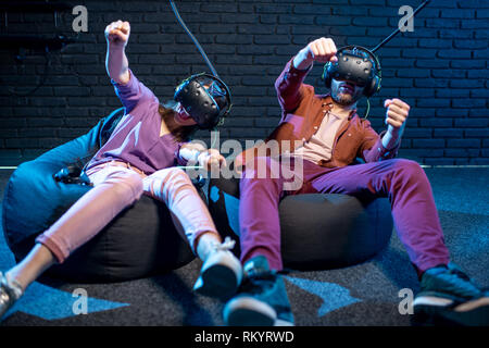 Man and woman playing in virtual reality simulating car driving using VR headsets in the playing room - Stock Image