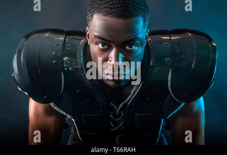 Portrait confident, tough football player wearing pads - Stock Image