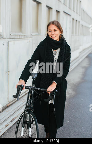 Smiling woman with bicycle - Stock Image
