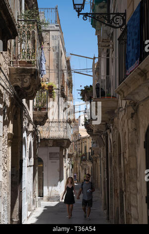 Street scene of young couple walking in ornate alleyway Via Dione in Ortigia, Syracuse, Sicily - Stock Image