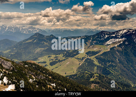 View from top of Mount Wendelstein in Upper Bavaria in the late Spring, featuring the Alps, pastures and fields at a distance - Stock Image