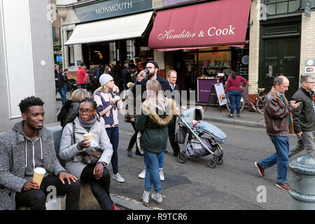 Borough Market street scene people drinking coffee and walking outside Konditor & Cook cake shop and Monmouth coffee shop London UK  KATHY DEWITT - Stock Image