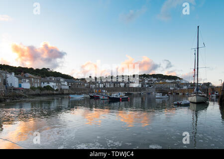Mousehole, Cornwall, UK. 19th June 2019. UK Weather. After days of grey skies and rain, the sunshine finally returned to Cornwall this afternoon and evening, with a fine end to the day at Mousehole Harbour. Credit Simon Maycock / Alamy Live news. - Stock Image