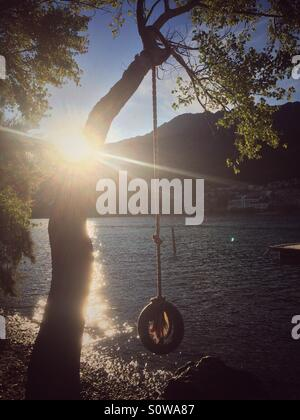 Tire swing over lake - Stock Image