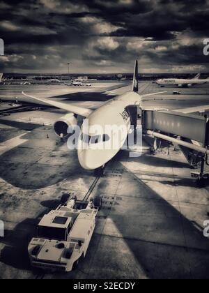 An aircraft sits underneath storm clouds at an airport in Europe. Has this plane just arrived? Is it about to depart? Photo Credit - © COLIN HOSKINS. - Stock Image