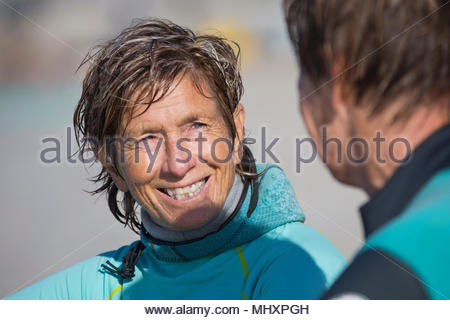 Senior surfers in wetsuits chatting to each other - Stock Image