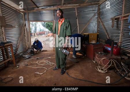 Rwandan welder in his metal and wood workshop, Kigali, Rwanda - Stock Image