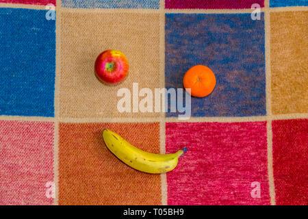 Apple, orange and a banana on a multi coloured squared rug. - Stock Image