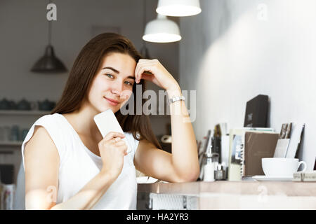 Beautiful girl mobile phone coffee shop - Stock Image