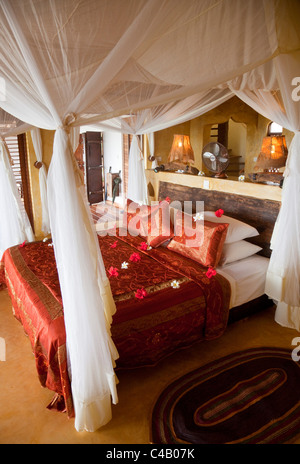 Zanzibar, Matemwe Bungalows. A four-poster bed in the centre of one of Matemwe's luxury suites. - Stock Image