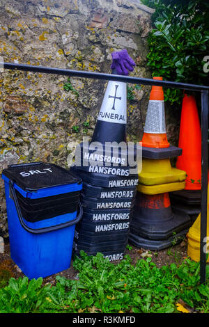 Hansfords funeral directors parking cones at the church at Branscpmbe village in East Devon UK - Stock Image