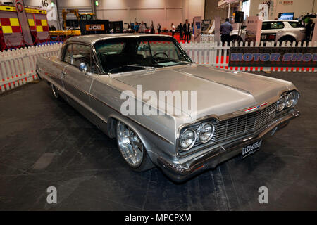 Three-quarter front view of a 1964 Silver, Chevrolet Impala, on display at the 2018 London Motor Show - Stock Image