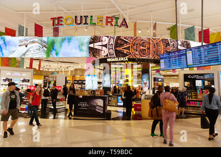 Passengers shopping for tequila in the Tequileria duty free shop, Cancun airport, Cancun Mexico - Stock Image
