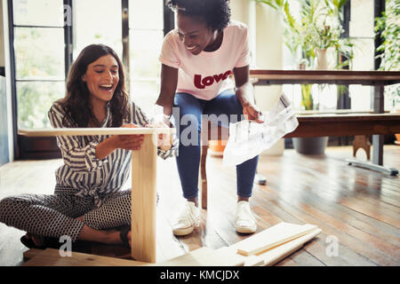 Women with instructions assembling furniture - Stock Image