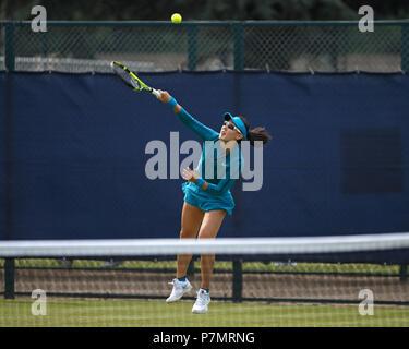 Professional female tennis player Saisai Zheng (Zheng Saisai) serving during a match. - Stock Image