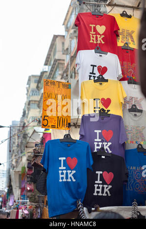 'I love HK' t-shirts hanging at a souvenir stall at the Ladies Market in the Mong Kok area of Kowloon, Hong - Stock Image