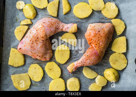 Raw Two Grilled Chicken Legs with Potatoes Ready to Cook. Organic Food. - Stock Image