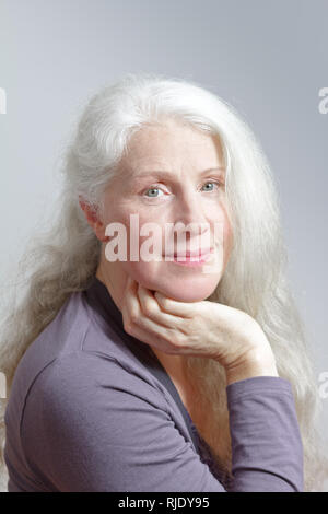 Portrait of an attractive mature woman with beautiful long white hair in front of gray background. - Stock Image