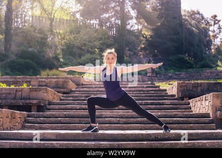 beautiful young woman doing yoga pose on the stairs of the park, morning workout outdoors, sports and healthy lifestyle - Stock Image