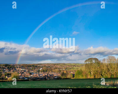 UK Weather: Snowbow rainbow over Ashbourne, Derbyshire as storms clouds approach over the gateway for the Peak District - Stock Image