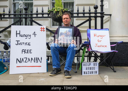 London, UK. 17th June, 2019. Richard Ratcliffe holding a photo of Nazanin and their daughter Gabriella stages a hunger strike outside the Iranian Embassy in London to protest against the continued imprisonment of his wife Nazanin Zaghari Ratcliffe who has been held on alleged spying charges Iran since 2016 in a five year prison sentence Credit which she denies: amer ghazzal/Alamy Live News - Stock Image