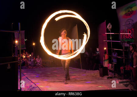 Young thai man makes fire circles as part of a beach side thai fire show. - Stock Image