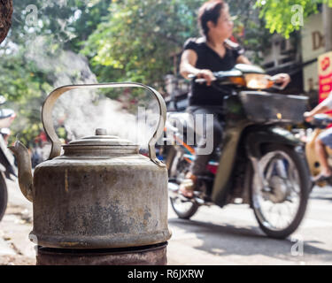 boiling water in old metal kettle on the street in Hanoi, Vietnam. Blurred background, unrecognizable woman on scooter. - Stock Image
