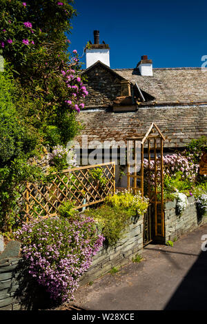 UK, Cumbria, Hawkshead, Wordsworth Street, tiny triangular garden in village centre with floral planting on wall - Stock Image