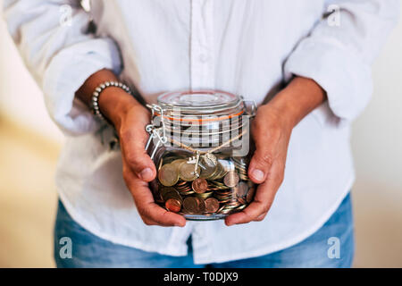 Close up of woman hands at home taking a transparent glass vase full of coins and airplane outside - economy and money for the next travel vacation -  - Stock Image