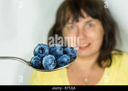 Fresh juicy blueberries with water drops on stainless spoon. Vaccinium myrtillus. Blue bilberries close-up. Woman on background. Alternative medicine. - Stock Image