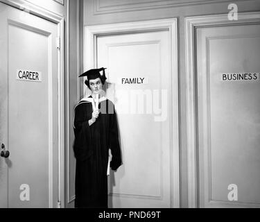 1950s COLLEGE GRADUATE WOMAN DECIDING ON FUTURE CAREER FAMILY BUSINESS - s1043 CLE003 HARS WEIGHING B&W CONCERNED PUZZLED FREEDOM GOALS ROBES CAREERS CHOICE DIRECTION RIGHTS OPPORTUNITY OCCUPATIONS DECIDE CONSIDER SELECTION DECIDING INDECISIVE WOMEN'S CHOICES CHOOSE DECISIONS GROWTH OPTIONS YOUNG ADULT WOMAN YOUNG ADULTS BLACK AND WHITE CAP AND GOWN CAUCASIAN ETHNICITY CHOOSING CONSIDERING OLD FASHIONED UNCERTAIN - Stock Image