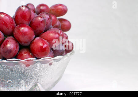 Bunch of Seedless Red Grapes in a Glass Bowl Offset - Stock Image
