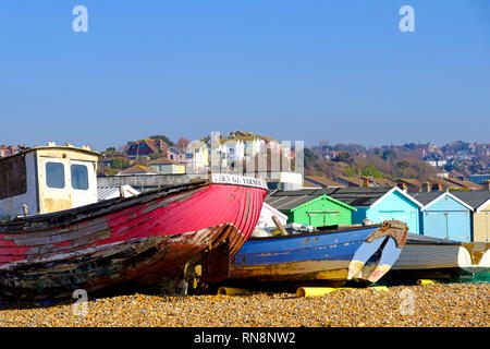 Old fishing boats and beach huts on the Bulverhythe beach, West St Leonards, East Sussex. UK - Stock Image