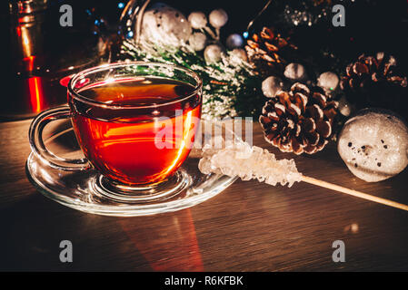 Hot cup of black tea with sugar on the table decorated with Christmas toys, pine branch and cones. Christmas mood - Stock Image