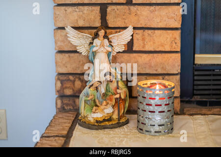 Christmas tabletop decor arrangement sitting on a fireplace hearth. Winged angel, mother Mary, Joseph, baby Jesus, lit candle. Nativity scene. - Stock Image