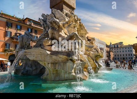 Rome, Italy - September 30 2018: Tourists visit the Fountain of the Four Rivers by Bernini in the Piazza Navona in Rome Italy as the sun goes down. - Stock Image