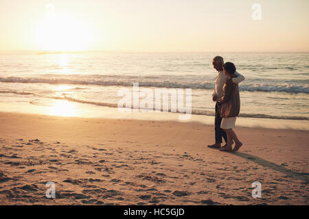 Shot of senior couple strolling on the beach at sunset. Senior man and senior woman taking a walk on the sea shore. - Stock Image