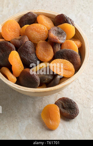 Bowl with a mixture of dried orange and brown apricots - Stock Image