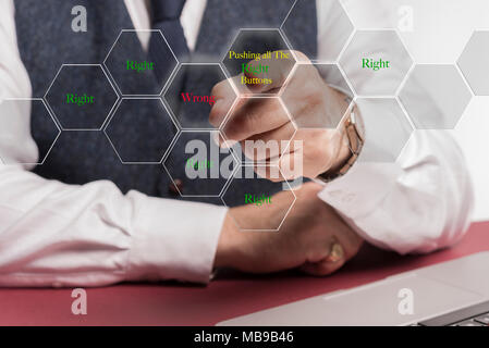 """A smartly dressed business man sitting at a desk whilst pushing a virtual button on the screen saying """" Pushing all the right buttons """" - Stock Image"""