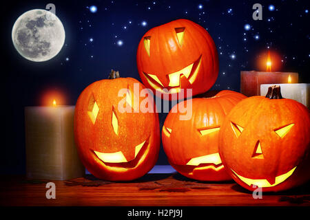 Halloween party decor, scary festive still life over starry sky background, carved pumpkin faces as jack-o-lantern - Stock Image