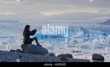 Profile view of woman photographing remote landscape and frozen glaciers in still ocean under cloudy sky - Stock Image