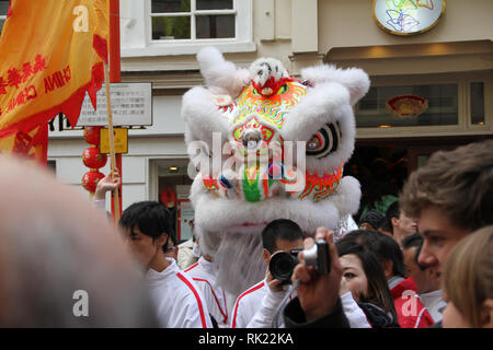 London, UK: 14 February 2010: Londononers seem amidst a chinese ceremonial dragon during the Chinese New Year celebration in London. Photo Credit: David Mbiyu - Stock Image
