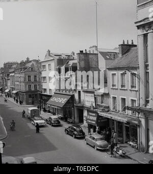 1950s, PCherbourg, France, french street showing a variety of shops, including Andre shoe shop and La Dauphone, Les Mures De Cherbourg. - Stock Image
