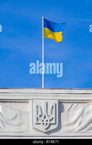 Flag and emblem of Ukraine on the roof of the building against the blue sky Kiev, Ukraine 06.11.2018 - Stock Image