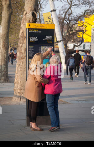 A mother and daughter look for directions on the South Bank by the Royal Festival Hall, London - Stock Image
