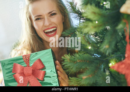 smiling trendy woman in red dress with green Christmas present box looking out from Christmas tree - Stock Image