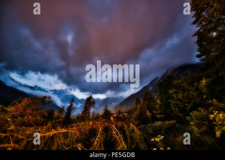 Colored clouds at sunset in mountains landscape with forest in foreground - Stock Image