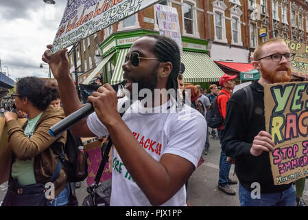 London, UK. 8th September 2018. A march through Brixton pauses for speeches at Brixton Market, calling for the Windrush scheme to be widened to include all families and descendants of the Windrush Generation and for an end to the racist hostile environment for all immigrants. It demanded an amnesty for those living here without secure immigration status and for free movement for Commonwealth Citizens. Credit: Peter Marshall/Alamy Live News - Stock Image